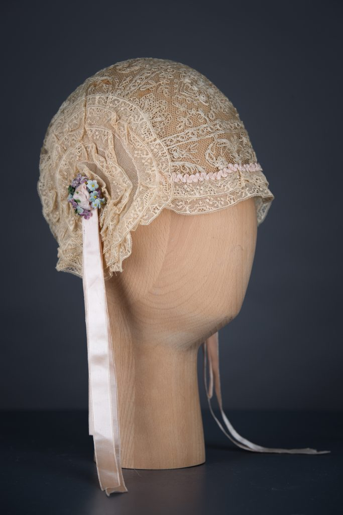 Lace ruffle and rosette boudoir cap. Front view. Photography by Tigz Rice Studios. From The Underpinnings Museum Collection.