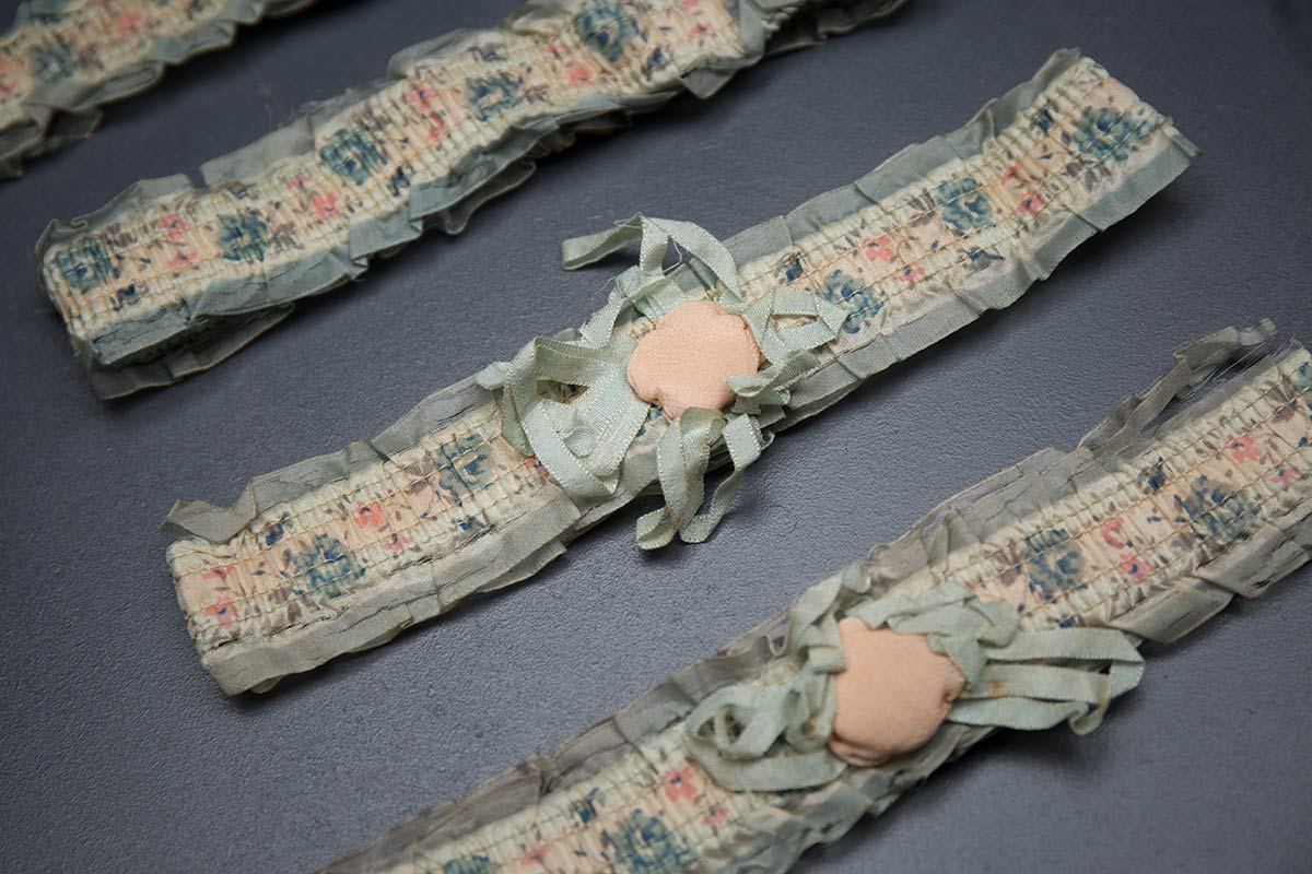 1920s floral ribbon garters with padding and rosettes, c. 1920s. USA Photography by Tigz Rice Studios. From The Underpinnings Museum collection.