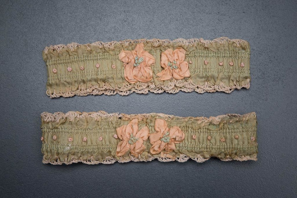 Green ribbon garters with crochet trim and French knot embroidery, 1920s, USA Photography by Tigz Rice Studios. From The Underpinnings Museum collection.