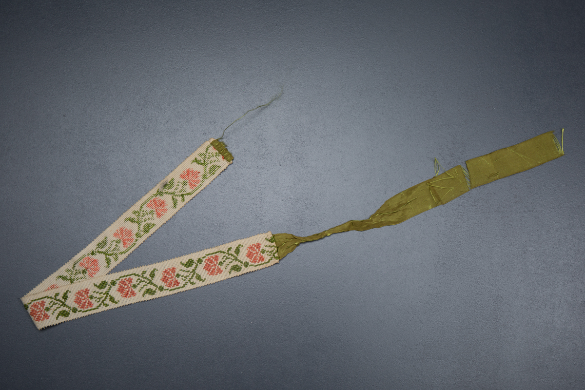 Cross stitch garter with ribbon tie, c. 1820s. From The Underpinnings Museum collection Photography by Tigz Rice