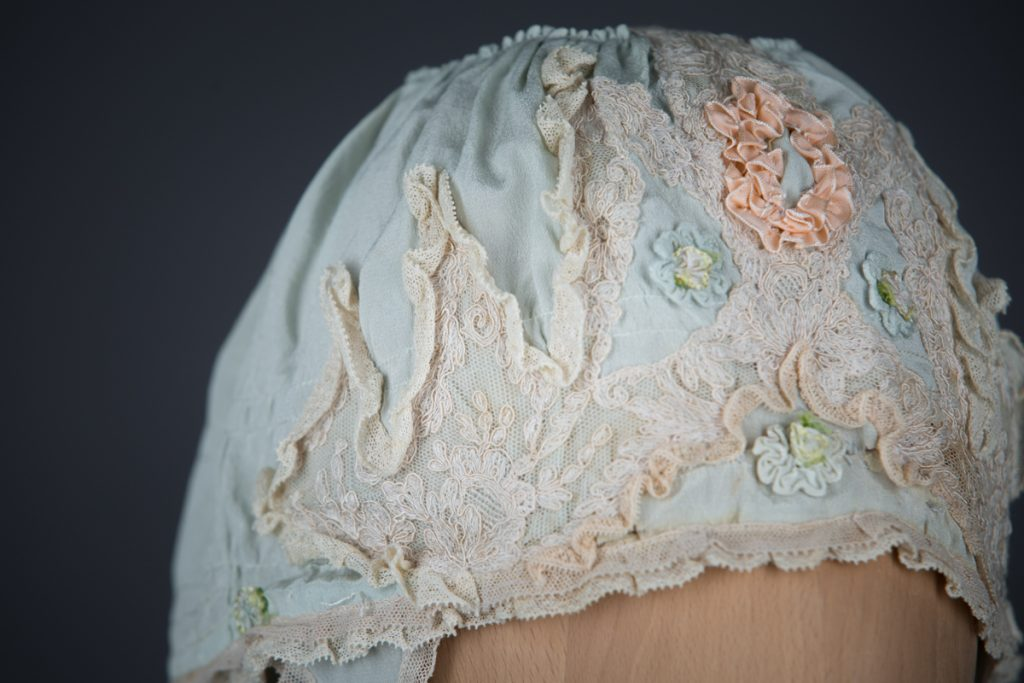 Pale blue silk boudoir cap with ribbonwork and lace, c. 1920s, GB. The Underpinnings Museum. Photo by Tigz Rice