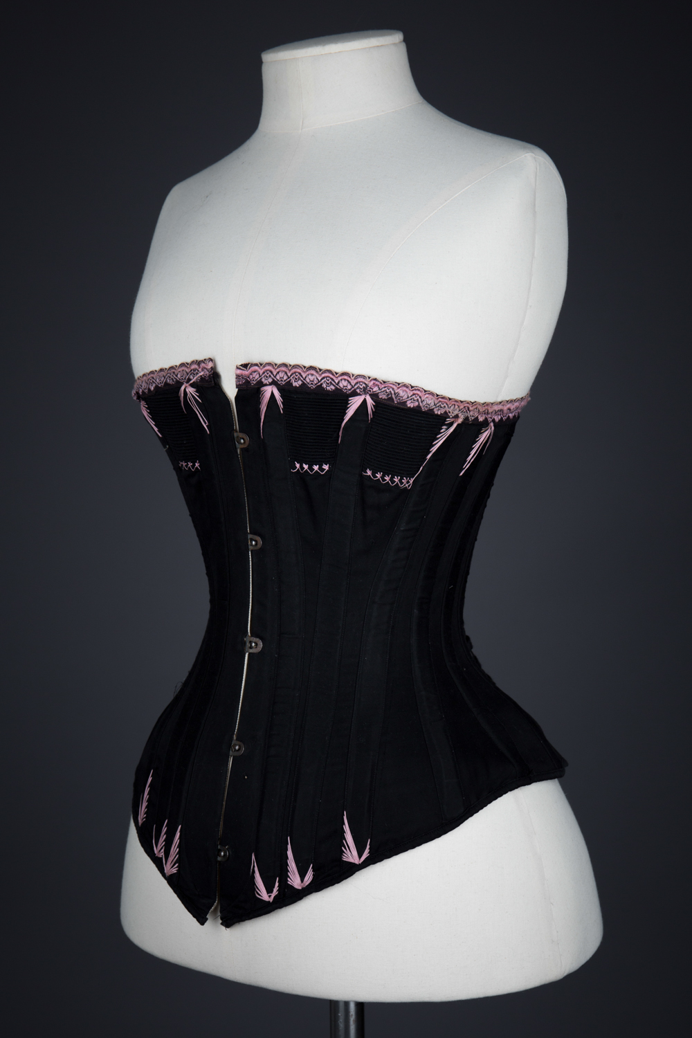 Black Cotton Corset With Spoon Busk, Pink Flossing Embroidery & Woven Trim, c. 1890-1900s, Great Britain. The Underpinnings Museum. Photography by Tigz Rice.