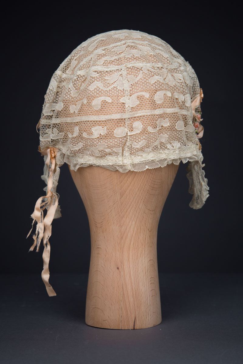 Cream Machine Lace Boudoir Cap With Silk Ribbonwork & Wired Ear Covers, c. 1920s, Great Britain. The Underpinnings Museum. Photography by Tigz Rice